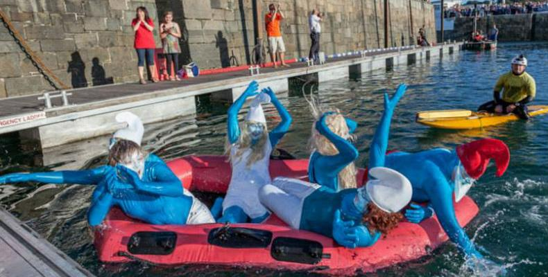 Ladies painted as smurfs paddling in St Peter Port Harbour during Harbour Carnival