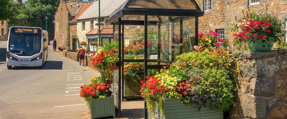 Bus driving past flowers in front of Forest Stores, Guernsey