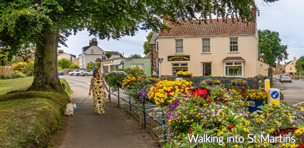 Lady walking dog beside floral St Martins
