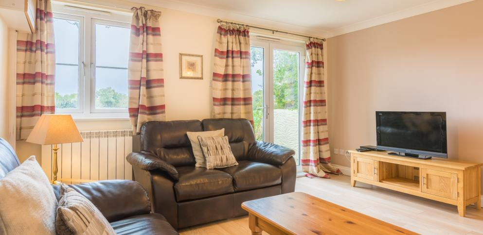 The living room with leather sofas in this two bedroom holiday cottage at The Ellingham Cottages in Guernsey