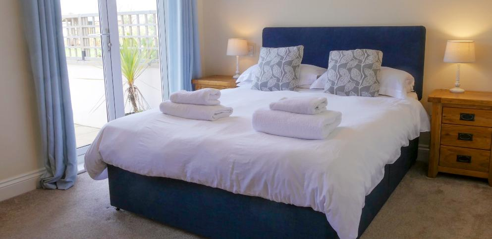 Blue double bed overlooking garden