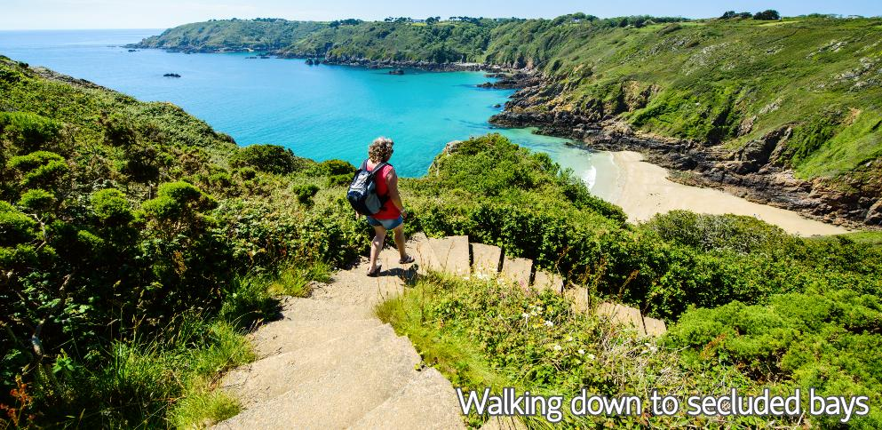 Lady walking down cliff paths to bay