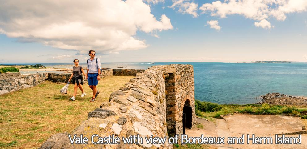 Couple walking on Vale castle with view of Bordeaux and Herm Island in background