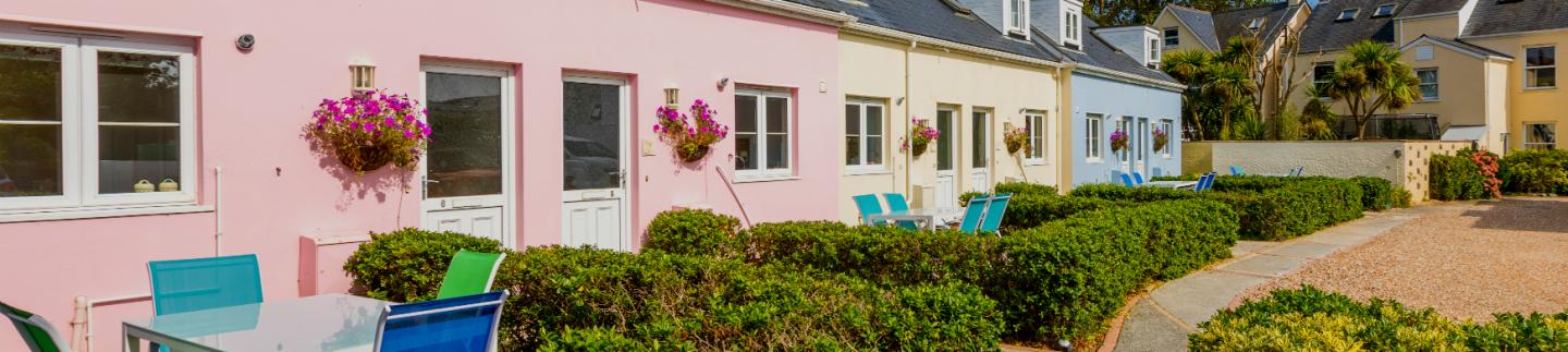 Exterior of the colourful holiday cottages - all are two bedroom self catering cottages in Guernsey.