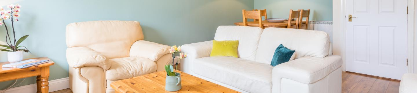 Living room with cream sofas in three-bedroom holiday cottage at The Ellingham Cottages in Guernsey