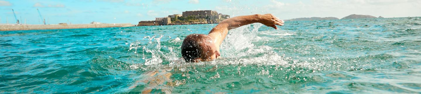 man swimming in sea in Havelet Bay in Guernsey