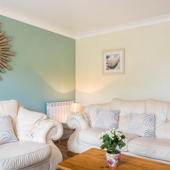 Guernsey self catering holiday cottage living room at The Ellingham Cottages.  Blue walls and comfortable sofas.