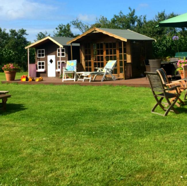 View of garden at the holiday cottage complex in Guernsey.  Chalets and plenty of places to sit and eat.