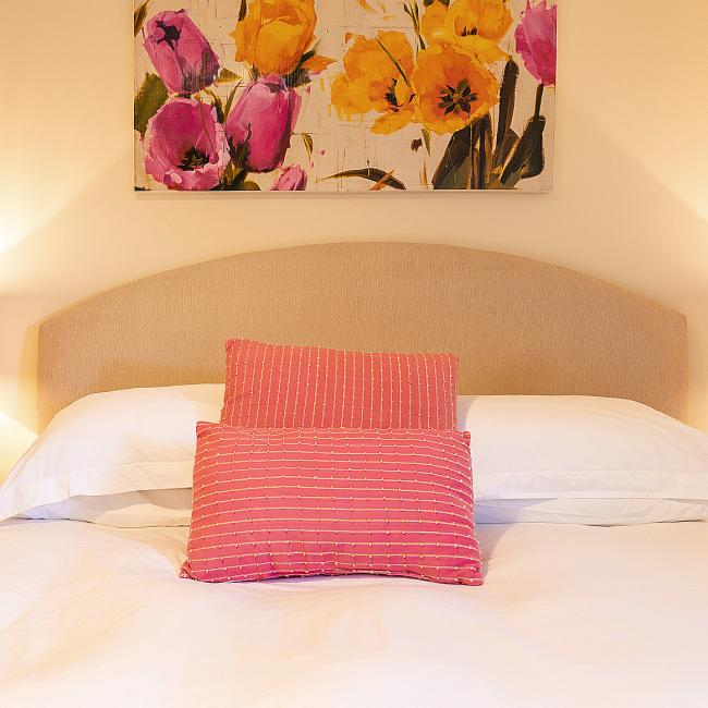 The bed in the master bedroom at The Ellingham Cottages