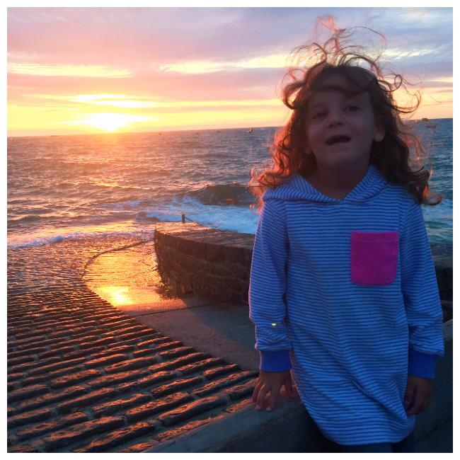 Girl in front of sunset in Guernsey