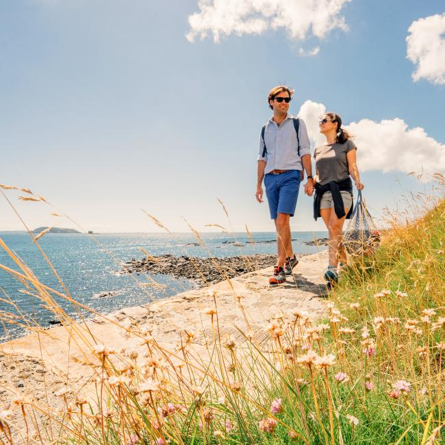 couple walking on the north coast in Guernsey