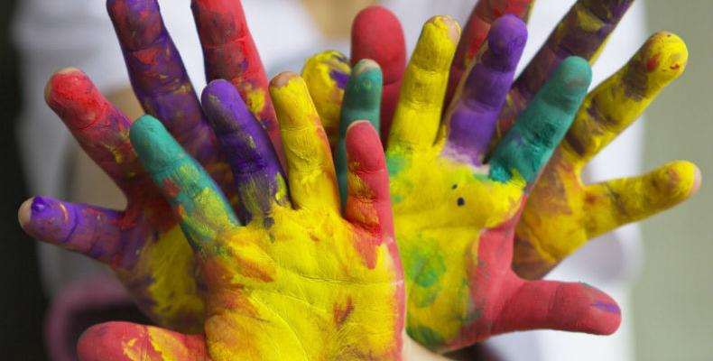 Children's hands covered in brightly coloured paint