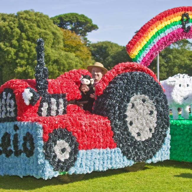 Tractor decorated with flowers in the Guernsey Battle of the Flowers parade.