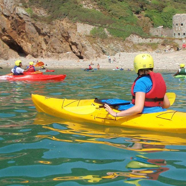 Person kayaking in sea at Fermain Beach in Guernsey, near to The Ellingham self catering cottages