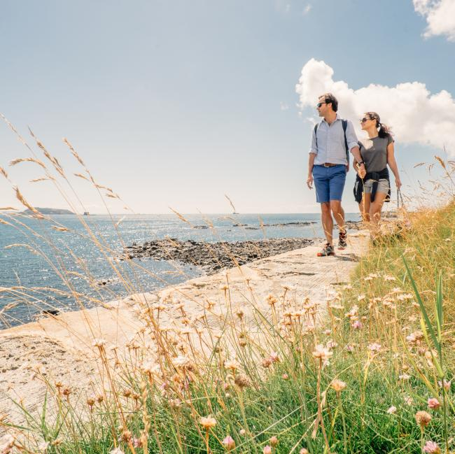 couple walking by the beach in the north of Guernsey
